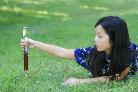 Portrait of a young asian female in traditional Vietnamese dress with sword Imagens