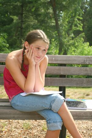 assignment: School girl thinking and working on difficult homework assignment in a park on a bench