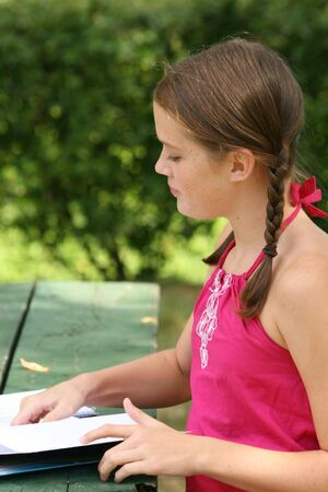 School girl writing in notebook, planner in an outdoors setting Stock Photo - 3491477