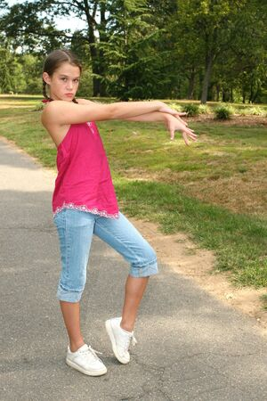 Young girl practicing dance moves on a path in a park, outdoor setting photo