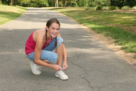 Young girl tying her shoes on a path in a park, outdoor setting photo