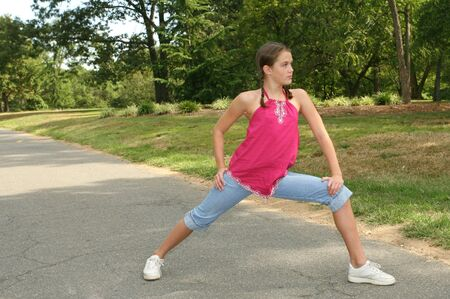Young girl practicing dance moves or stretching on a path in a park, outdoor setting photo