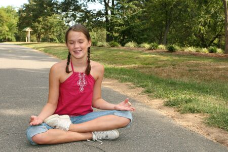 Young girl practicing yoga poses on a path in a park, outdoor setting photo