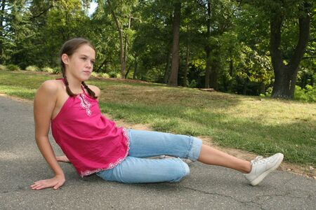 Young girl sitting down or stretching on a path in a park, outdoor setting photo