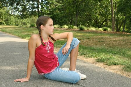 Young girl relaxing, sitting on a path in a park, outdoor setting photo