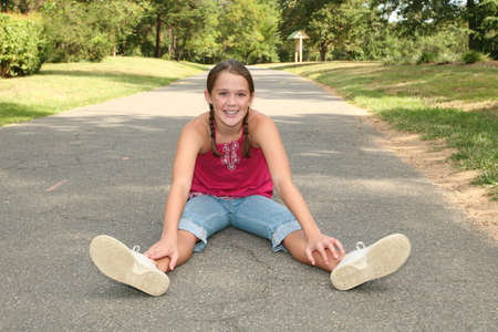 stopped: Smiling, happy, approachable teen or preteen girl sitting on  a path in a park, outdoors