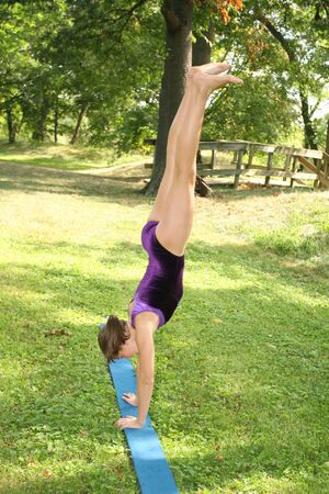 Young girl doing gymnastics exercisesworkout in a park photo