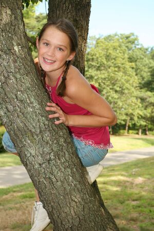 preteen girls: Young girl having fun climbing a tree in a park