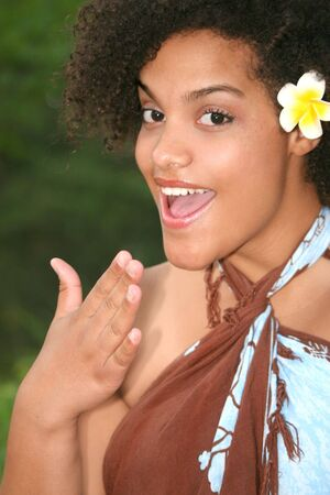 Portrait of a beautiful young female with hibiscus in her hair, Hawaiian theme