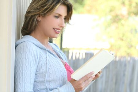 Beautiful woman reading a book outdoors, in a park setting Imagens - 3656758
