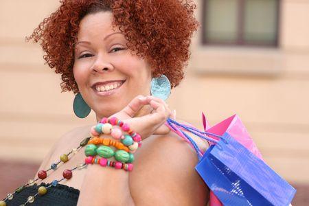 Plus dimensioni modello, sorridente su un acquisto e la ricerca in una shopping bag. Archivio Fotografico - 3765301