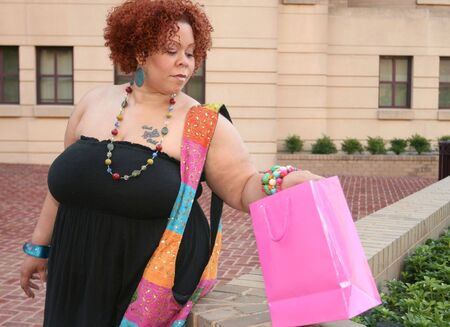 body jewelry: Plus size model, smiling about a purchase and looking into a shopping bag.