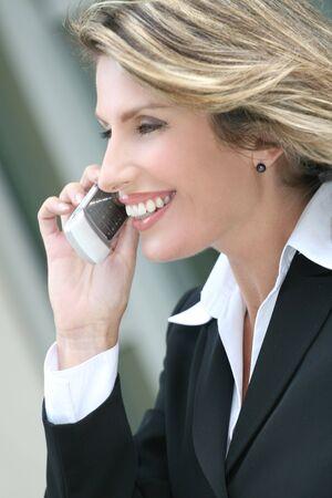 적합: Headshot of an attractive, laughing corporate female in a suit on a cell phone. Suitable for a variety of commercial, finance and business themes.