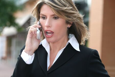 Attractive business woman is worried, on cell phone, thinking about a problem, suitable for economic and financial crisis theme.
