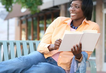 thinking woman: Attractive, young African-American female reading a book outdoors on a bench, street view, urban environment