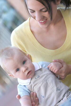 적합: Young mother holding her baby son, suitable for a variety of family, parenting, motherhood, childhood themes