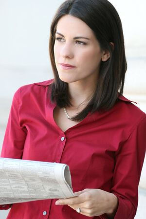 Attractive Caucasian business woman reading a newspaper. Suitable for a variety of economic and political themes photo