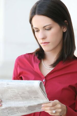 Attractive business, corporate woman reading a newspaper outdoors Фото со стока