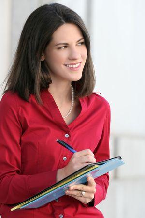 D'affaires, femme d'entreprise avec des dossiers, bloc-notes et crayon, la r�flexion sur les probl�mes �conomiques, � l'ext�rieur