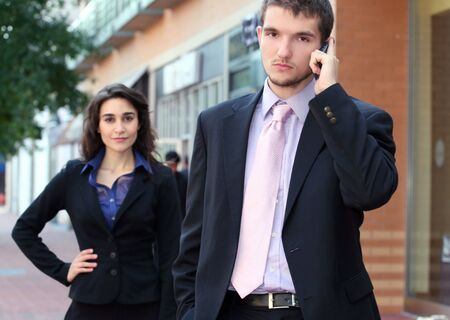 politican: Two young professionals, business, people, male in the front in focus on cell phone