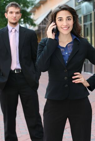 politican: Two young professionals, business, people, female in the front in focus on cell phone, male in the background Stock Photo