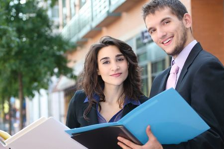 Two business people, young professionals, outdoors, at work - looking at folders. Suitable for a variety of political, economic themes Stock Photo