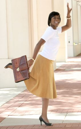 Beautiful African American Business, Corporate woman outdoors in front of a corporate building having fun, greeting somebody