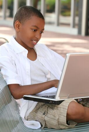African American Teenager Boy on Laptop Computer Outdoors on a bench, city street, urban setting Фото со стока