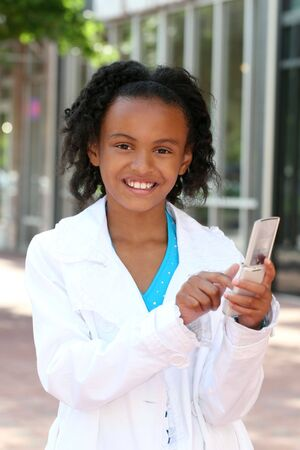 Smiling African American Teenager Girl on Cell Phone, texting or dialing