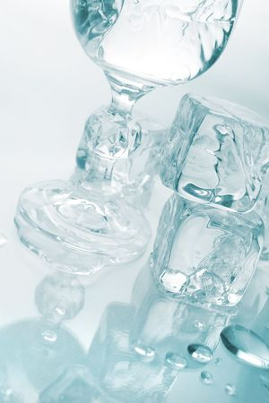 monotone: Melting ice cubes and glass with drink and ice, with reflection over monotone blue background Stock Photo