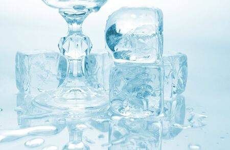 Melting ice cubes and glass with drink and ice, with reflection over monotone blue background Stok Fotoğraf