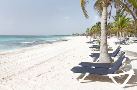Empty white sand beach, ocean and palm trees in Mexico, Riviera Maya photo