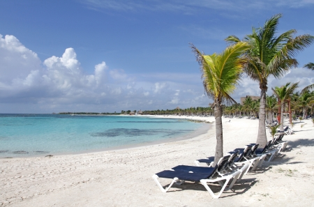 carribean: Empty white sand beach, ocean and palm trees in Mexico, Riviera Maya Stock Photo