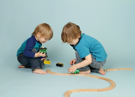 Kids playing with toy trains, playtime, games, sharing Imagens