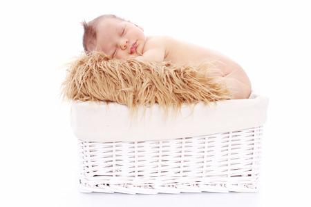 Newborn baby sleeping on fur in a basket on white background