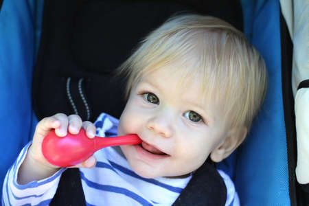 teething: Child, Baby boy in stroller, teething and biting a toy Stock Photo