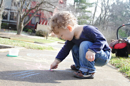 Child, toddler boy drawing with chalk on a sidewalk