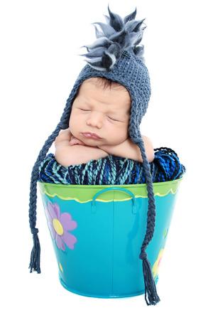 Newborn baby sleeping in a basket on white background