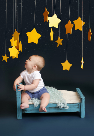 Baby sitting in bed, looking up, against a dark blue background  Nap time, sleeping concept