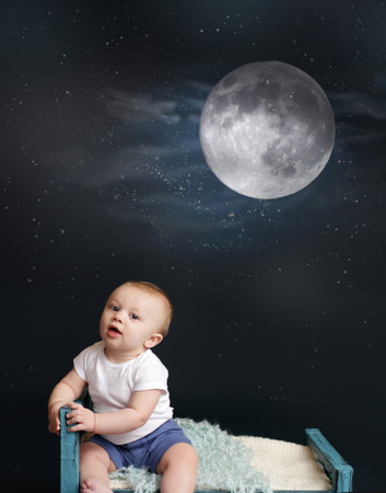 naptime: Baby sitting in bed, looking at moon and stars, against a dark blue background  Nap time, sleeping concept