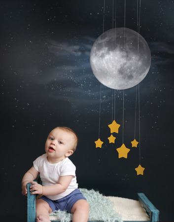 Baby sitting in bed, looking at the moon and stars mobile, starry night  Nap time, sleeping concept Stock Photo