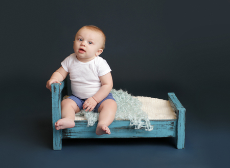 baby bed: Baby sitting in bed, looking at camera, against a dark blue background  Nap time, sleeping concept Stock Photo