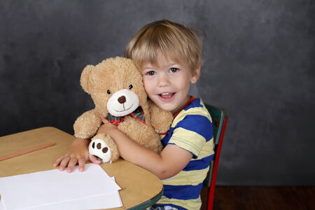stuffed animals: Back to School concept, child on chair in classroom hugging a stuffed bear toy