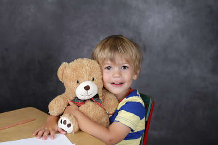 Back to School concept, child on chair in classroom hugging a stuffed bear toy photo