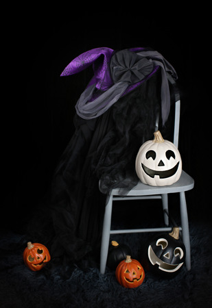 pointy hat: View of Halloween Pumpkins, a witchs hat and a cape on a chair against a dark background Stock Photo
