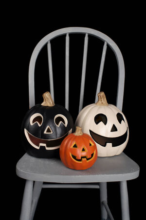 pointy hat: View of Halloween Pumpkins on a chair against a dark background