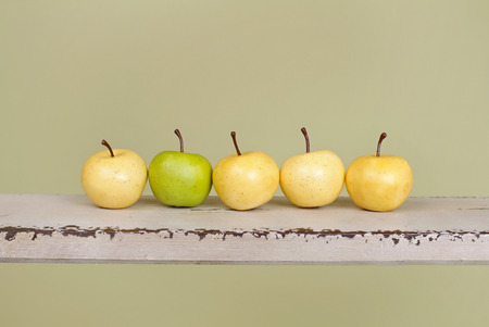 similarity: Row of apples on rustic wood bench, concept for teamwork, team, similarity and difference