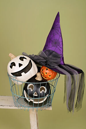 View of Halloween Pumpkins in a wire basket on a rustic wood bench photo