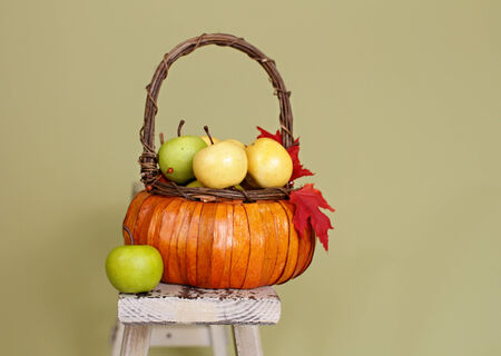 Apples and pumpkins in weave orange baskets, decorated with flowers and fall leaves, on rustic wood bench againt light green background photo