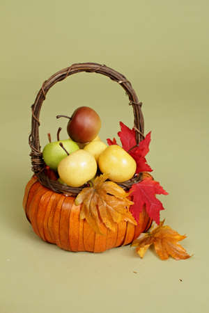 Apples and pumpkins in weave orange baskets, decorated with flowers and fall leaves, on rustic wood bench againt light green background